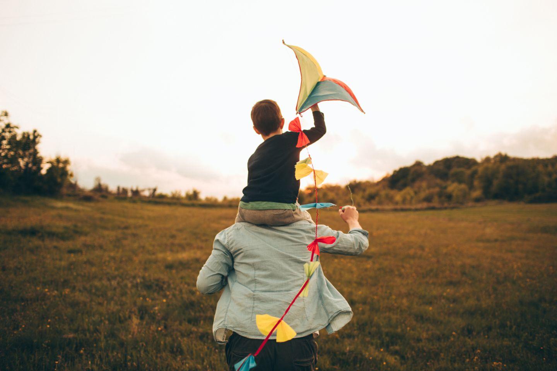 Kind auf den Schultern seines Vaters, Drachen fliegen