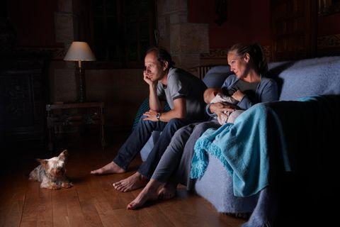 Frau stillt nachts beim Fernsehen