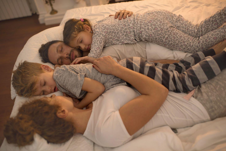 Familie schläft in einem Bett