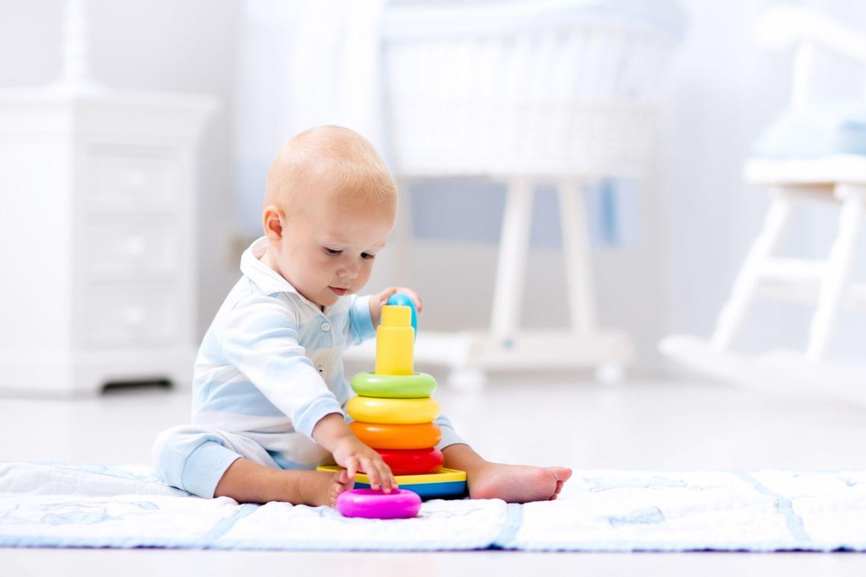 Baby spielt mit bunter Pyramide