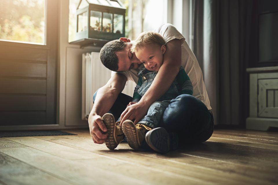 Vater kuschelt mit seinem Sohn
