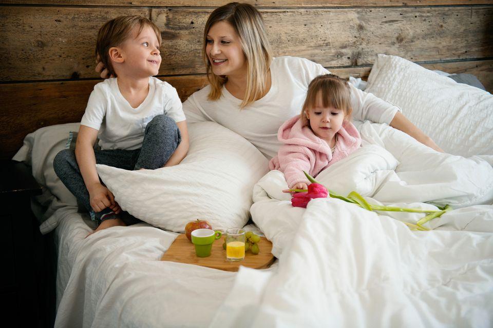 Mutter frühstückt mit kleinen Kindern im Bett