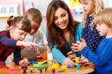 Kinder spielen mit Erzieherin an einem Tisch