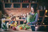Mutter schneidet Salat in der Küche und redet mit Kleinkind