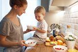 Mutter gibt Kind in der Küche eine Schüssel mit Joghurt und Obst
