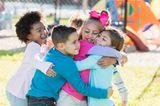 Mehrere Kinder umarmen sich auf einem Spielplatz