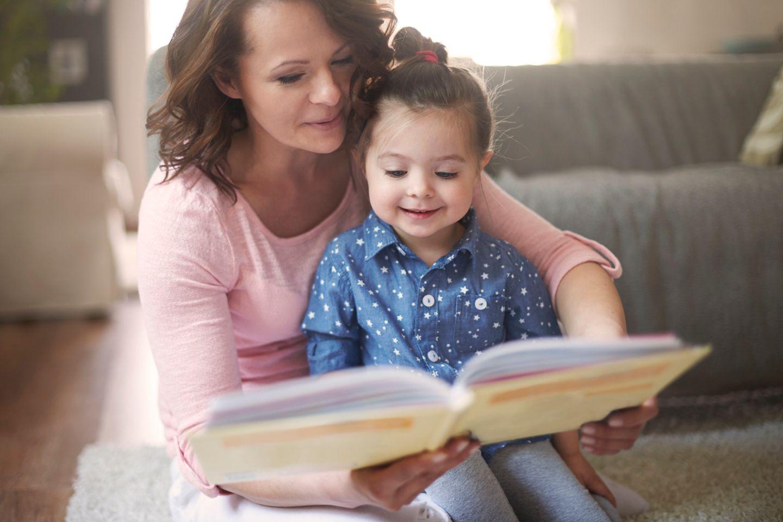 Mutter ließt Kind aus einem Buch vor