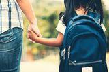Mutter bringt Kind zur Schule und hat es an der Hand