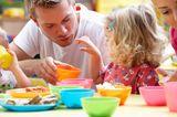 Vater hält Tochter am Frühstückstisch eine Schale mit Leckereien hin