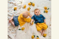 CARLA, 5 MONATE (LINKS), trägt einen Biobaumwoll-Jumpsuit, 12,99 Euro, von Topomini bei Ernsting's family; Baby Cardigan aus Biobaumwolle, 56 Euro, von FUB. HELENA, 6 MONATE (RECHTS), hat ein Vögelchen-Oberteil aus Baumwolle und Leinen an: 52 Euro, von Bobo Choses über Kleines Karussell; Strickhose, 45 Euro, von FUB. Accessoires: Zitronen-Decken von konges slojd über Kyddo; weiße Decke von Numero 74; handgehäkelte Zitronen-Rasseln von Sebra.