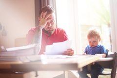Ein Vater mit Kind blickt verzweifelt auf eine Rechnung