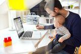 Eine Mutter mit Kind auf dem Schoß erledigt Büroarbeit