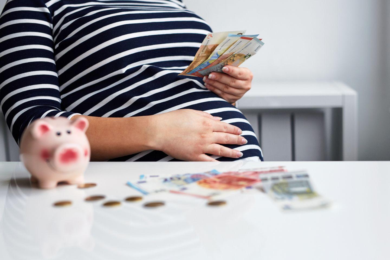 Eine Schwangere hält Geldscheine in der Hand