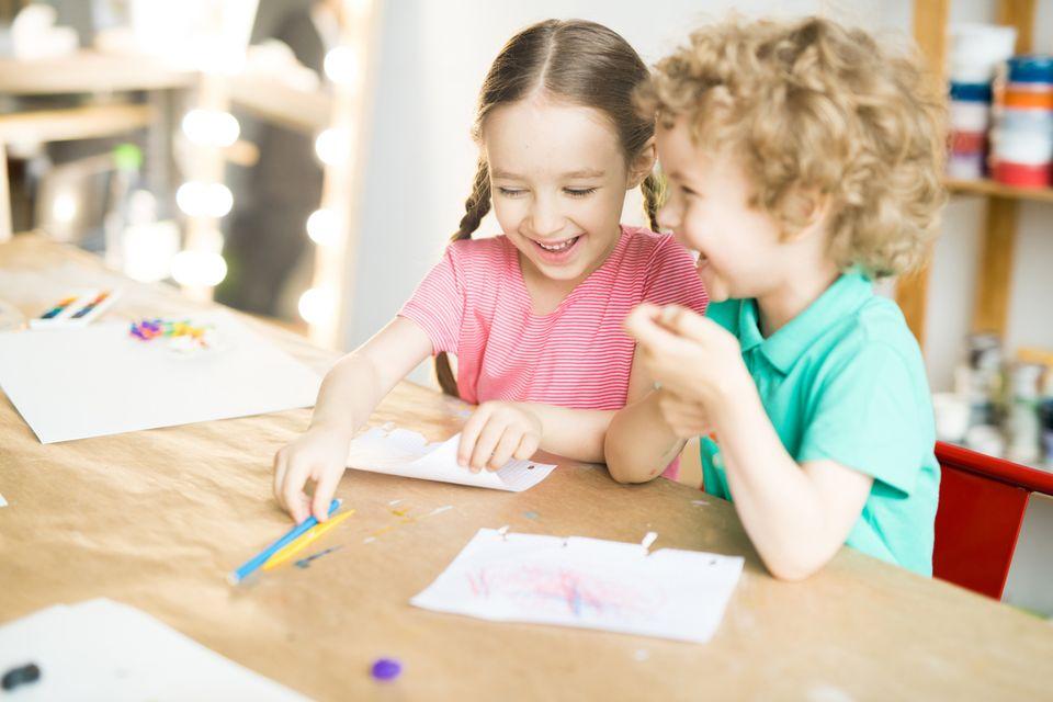 Kinder kichern beim Malen