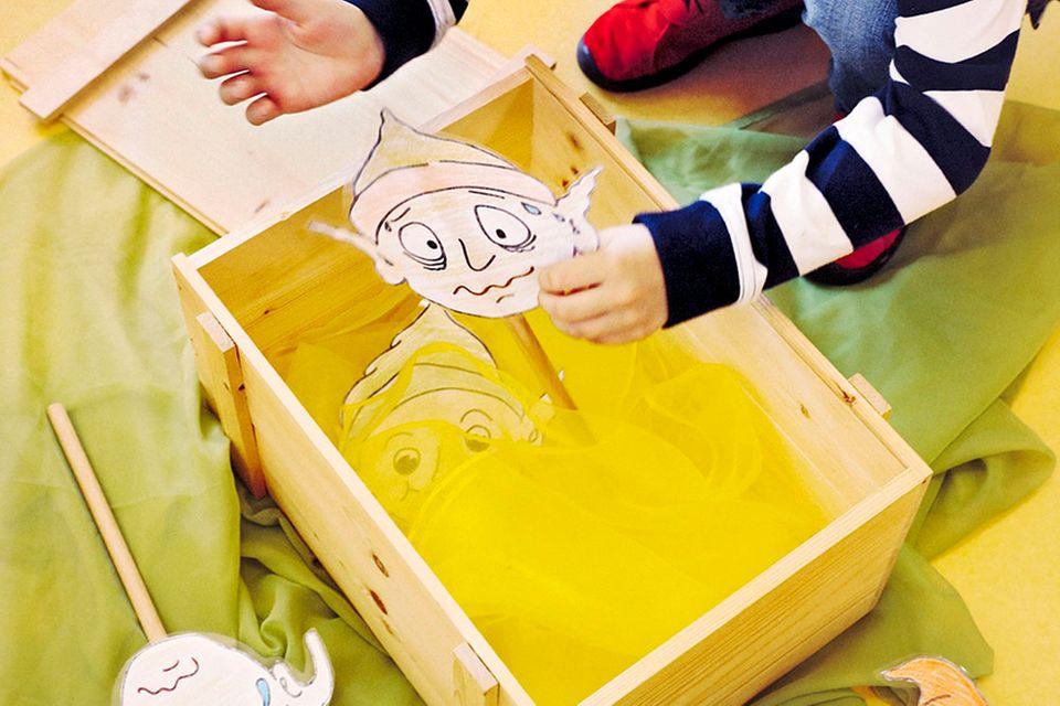 kleiner Junge packt Koboldpuppen aus