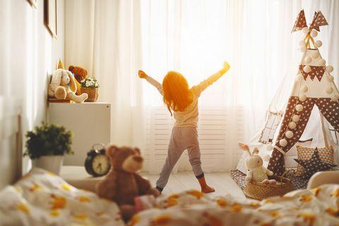 Kind ist aufgestanden und streckt sich im Kinderzimmer