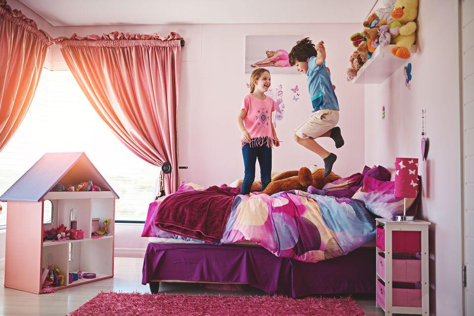 Zwei Kinder springen auf dem Bett herum
