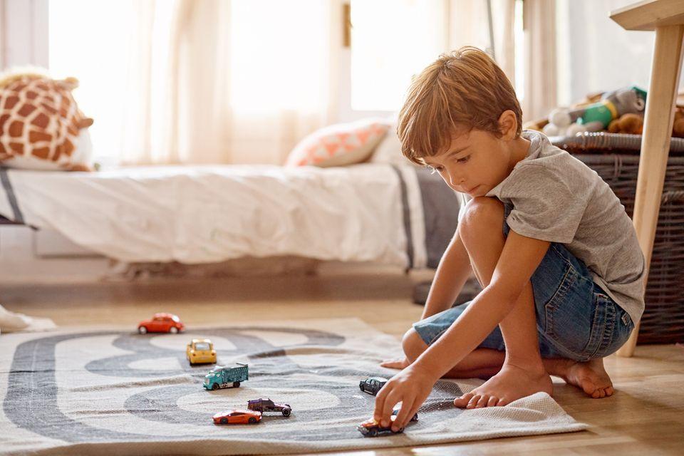 Junge spielt auf dem Teppich mit Autos
