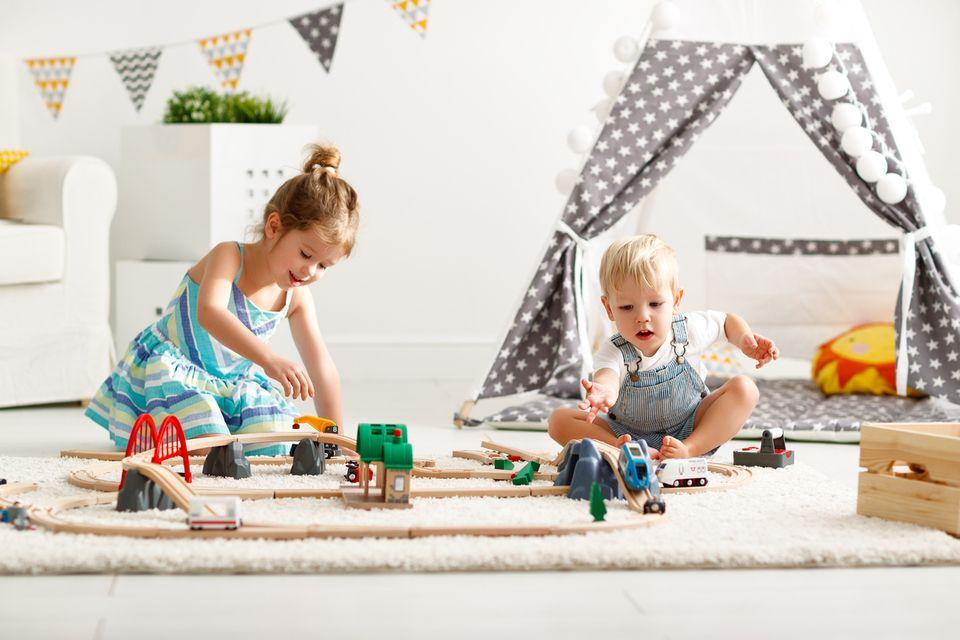 Zwei Kinder spielen in einem Zimmer Eisenbahn