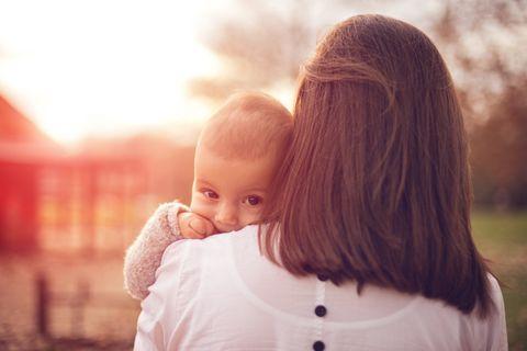 Frau mit Baby über der Schulter