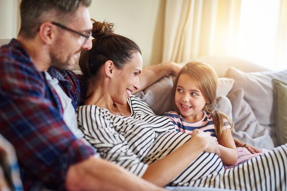 Eine Frau ist schwanger und freut sich mit Mann und Tochter auf Baby Nummer 2.