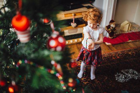 Kleinkind unterm Weihnachtsbaum mit Geschenken