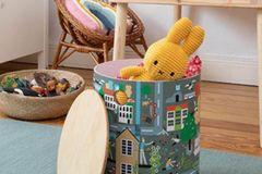 """Ein toller Hingucker im Kinderzimmer: der bunte Kinderhocker """"Meine grüne Stadt"""". Der ca. 30 cm hohe Hocker mit den schönen Illustrationen ist nicht nur eine prima Sitzgelegenheit, sondern bietet auch jede Menge Platz für Spielsachen. In einer Werkstatt für Menschen mit Behinderung wird der Artikel fair und nachhaltig hergestellt."""