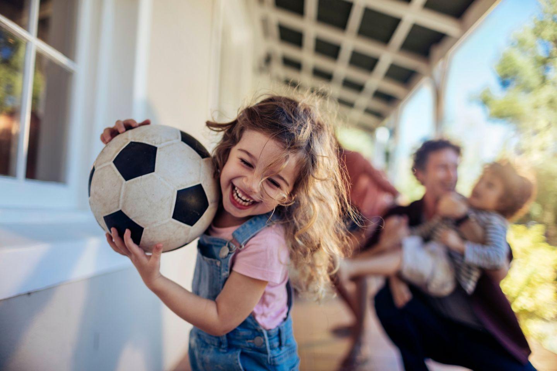 Mädchen läuft lachend mit Fußball weg