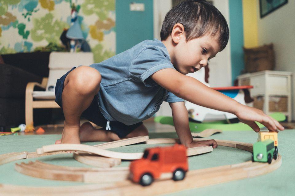 Kleiner Junge spielt mit der Holzeisenbahn