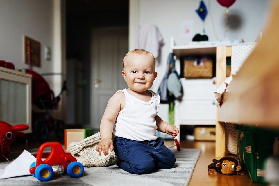Babyjunge sitzt zwischen seinen Spielsachen