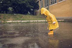 Kind spielt im Regen