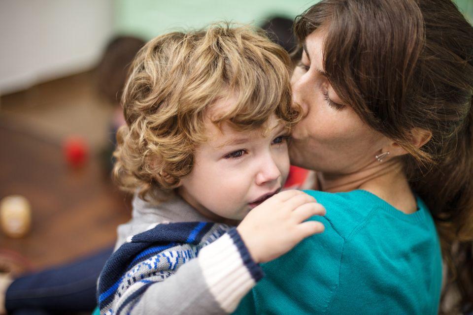 Eine Mutter tröstet ihr weinendes Kind.