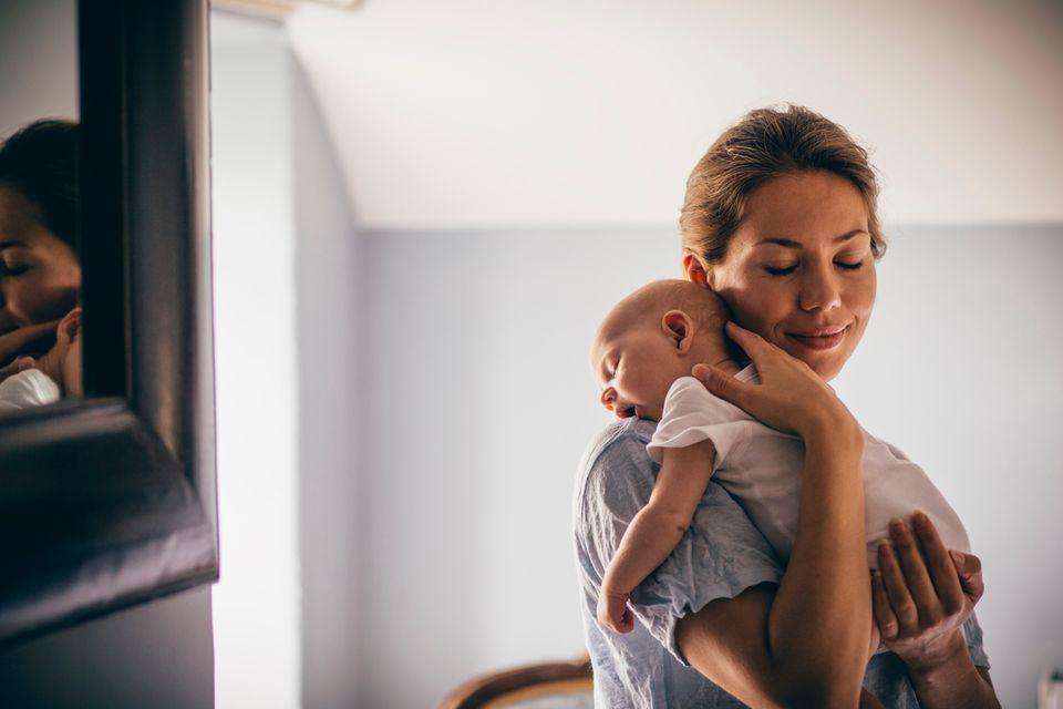 Eine Mutter hält ihr schlafendes Neugeborenes und es kuschelt sich in ihre Nackenhöhle.