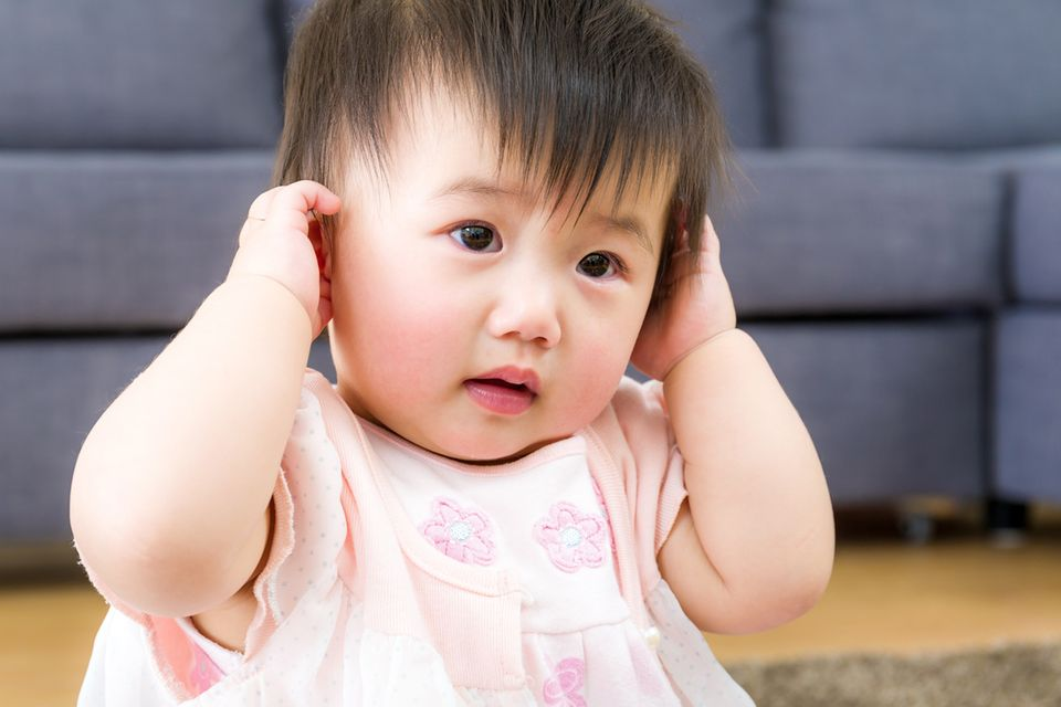 Kleines asiatisches Mädchen hält sich die Ohren