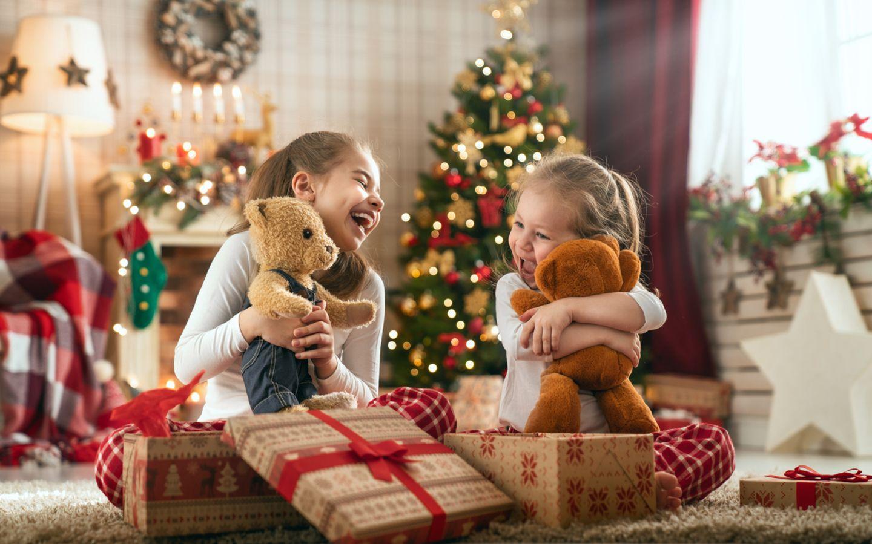 Zwei Mädchen packen begeistert ihre Weihnachtsgeschenke aus