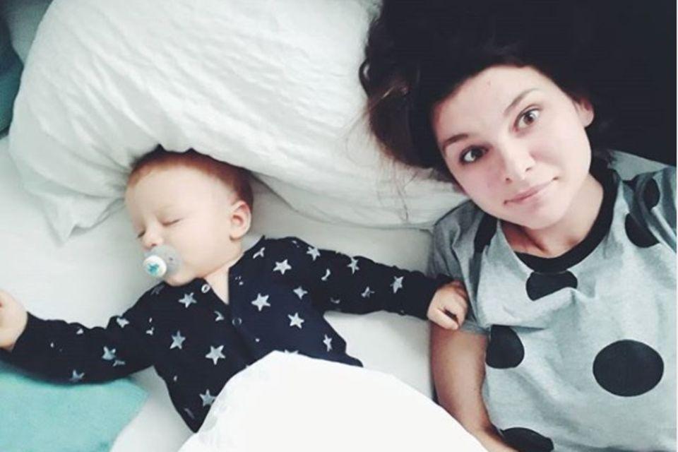 Mutter liegt neben schlafendem Baby