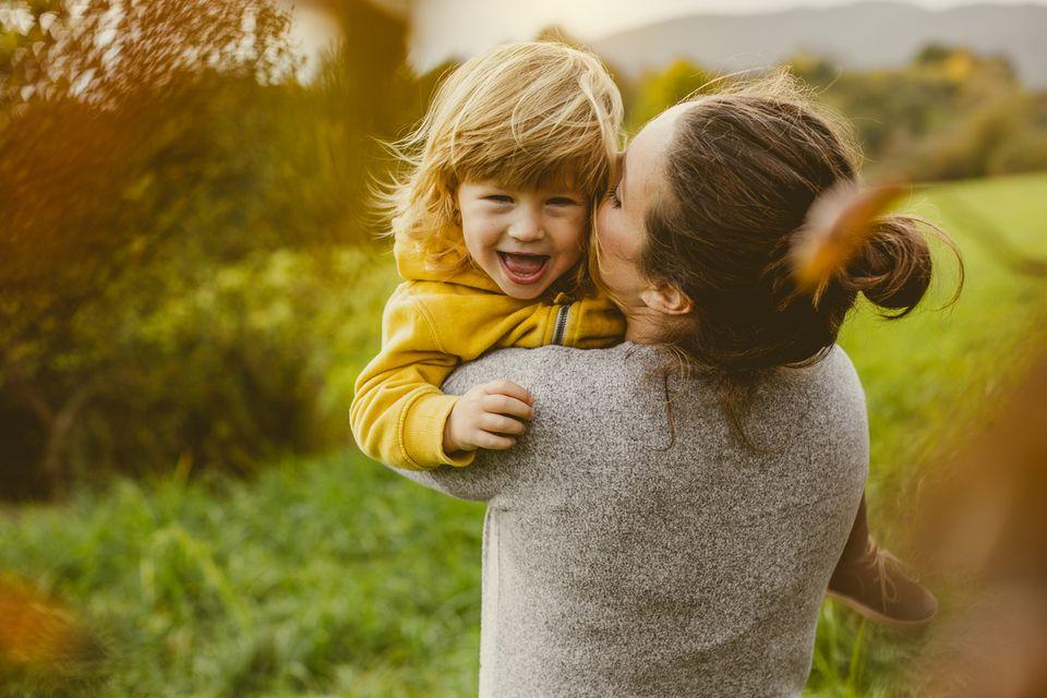 Junge Mutter hält ihr Kleinkind auf dem Arm