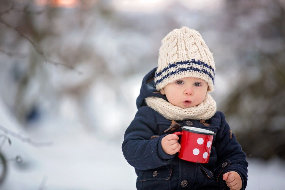Baby trinkt im Winter draußen Tee aus einem Becher