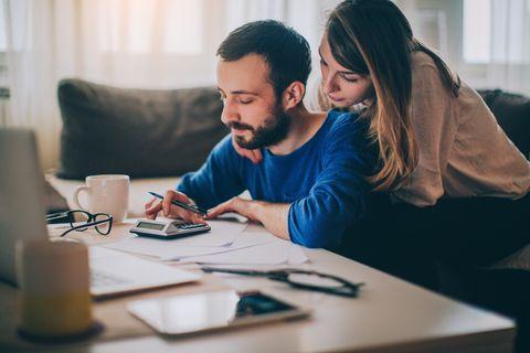 Ehepaar guckt auf einen Laptop und kalkuliert seine Finanzen