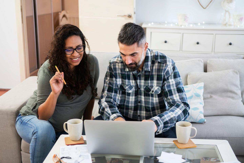 Eine schwangere Frau und ihr Partner sitzen zusammen vor einem Laptop und kalkulieren Elterngeld