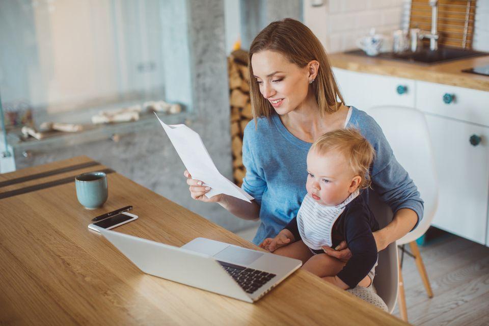 Mutter erledigt Papierkram mit ihrem Kleinkind auf dem Schoß