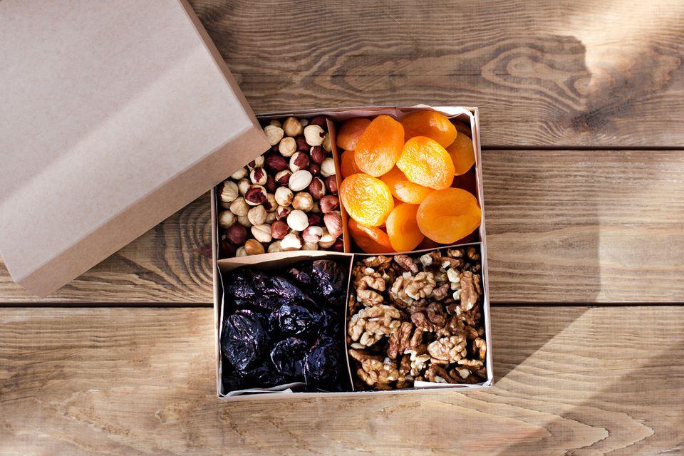 Eine Box mit Knabberzeug gegen Schwangerschaftsübelkeit: getrocknete Früchte, Nüsse