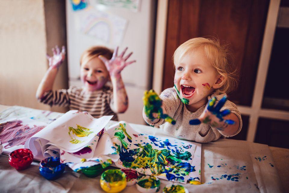 Glückliche Kita-Kinder malen mit Fingerfarben