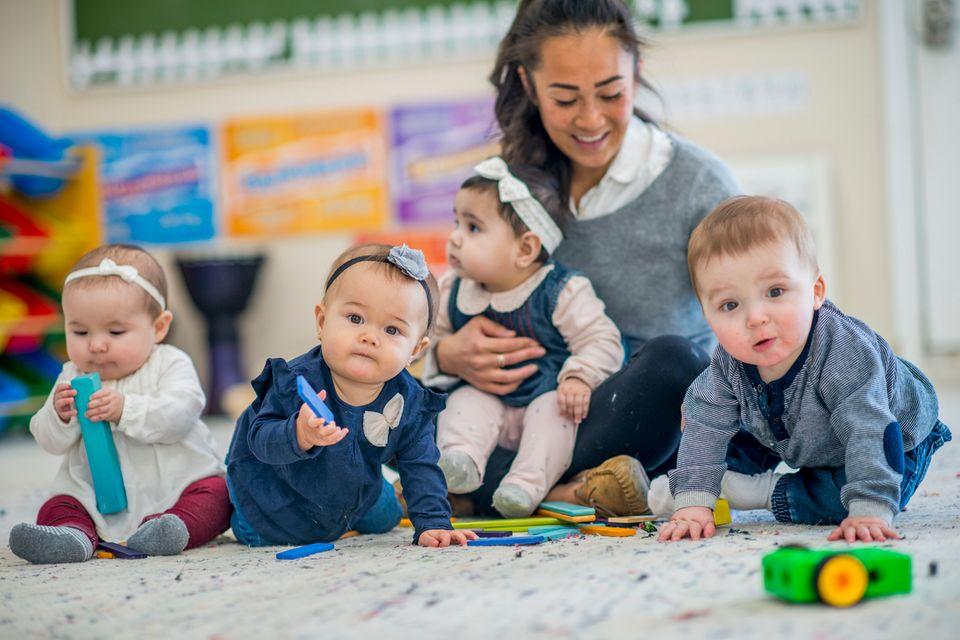 Eine Erzieherin spielt mit vier Babys auf dem Teppich