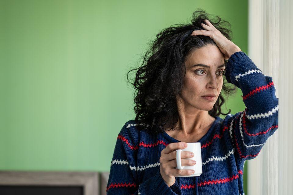 Besorgte Frau mit Kaffeebecher