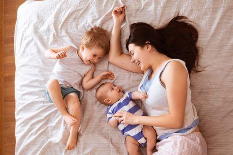 Eine Mutter liegt mit ihren zwei kleinen Kindern fröhlich lachend auf dem Bett