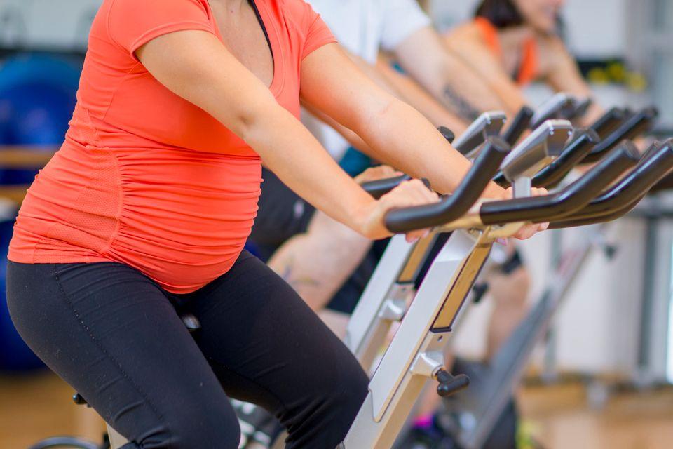 Schwangere-auf-fährt-Fahrrad-auf-einem-Heimtrainer