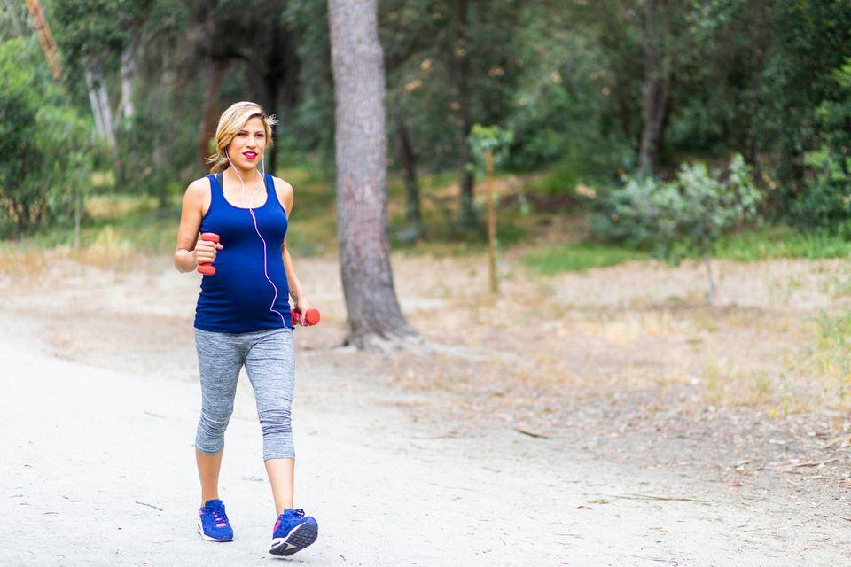 Schwangere-walked-mit-Hanteln-durch-Park