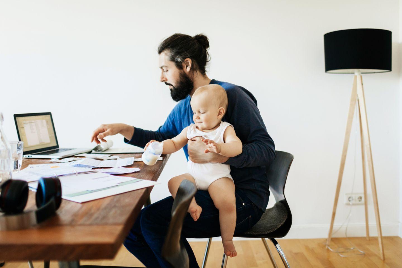 Vater arbeitet im Home Office und hat dabei sein Baby auf dem Schoß