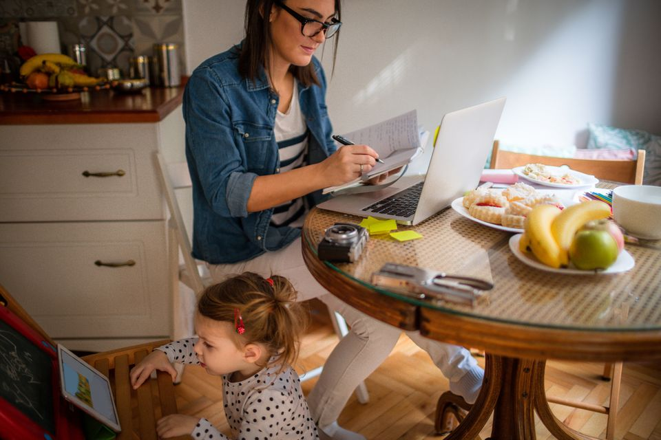 Mutter arbeitet am Laptop im Home Office, die Tochter spielt am Tablet
